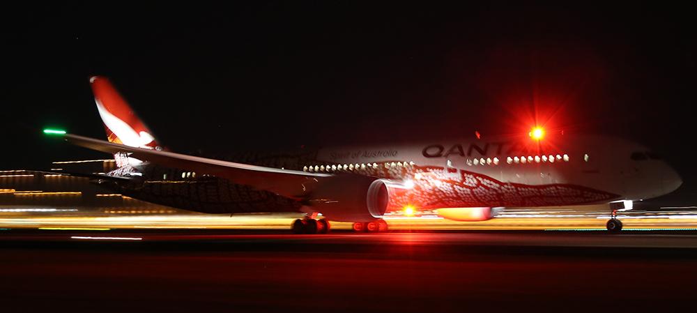 Long haul flights - night time shot of Qantas Dreamliner departing LHR