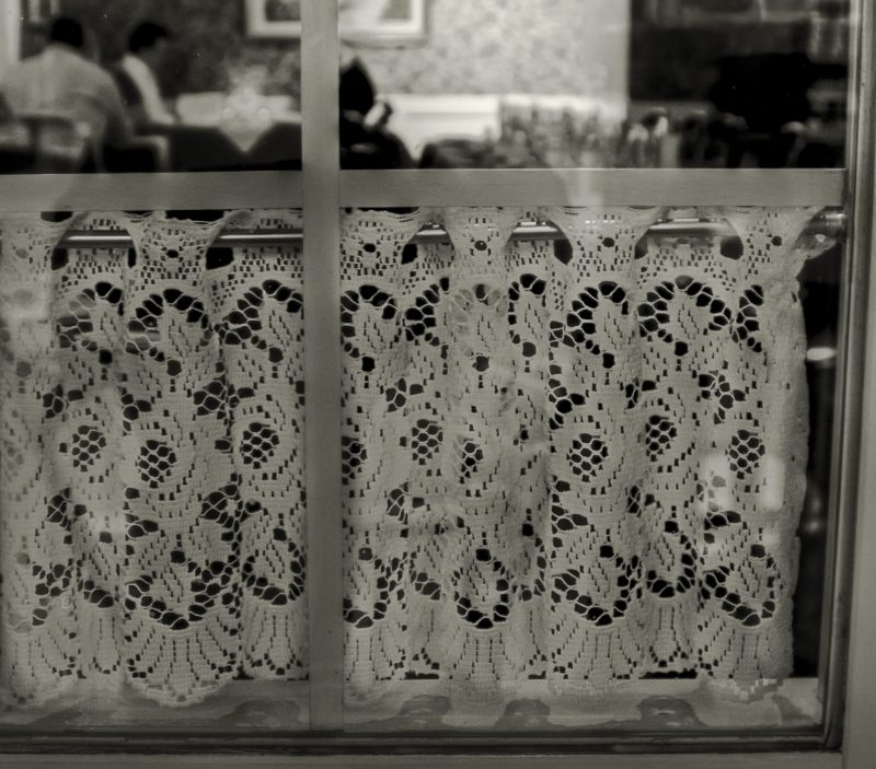 Bistro window with lace courtain in Quebec, Canada