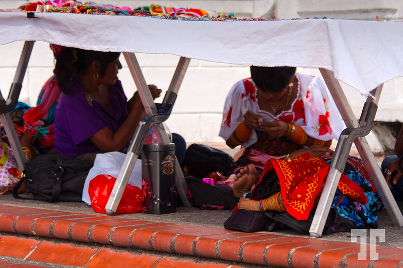 Kuna crafters hiding from the sun in Casco Viejo Panama, while working on their crafts