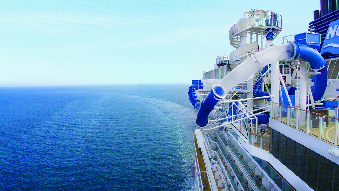 A water thrill ride loops over the side of the ship.