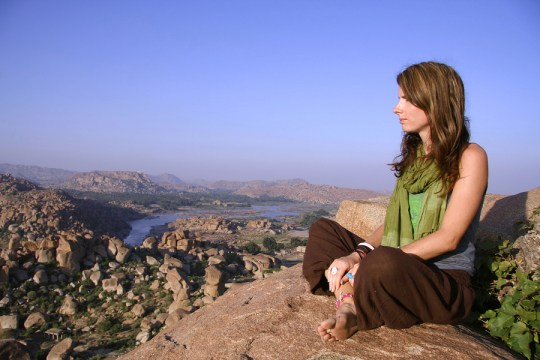 woman meditating at sunset on hilltop in hampi, india - enlightenment