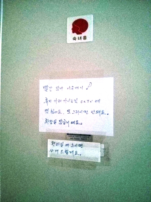 Note Reads: To the lady in the red jumper: We caught you stealing toilet paper from here on CCTV. If you come to the front office, we will give you 10 rolls!