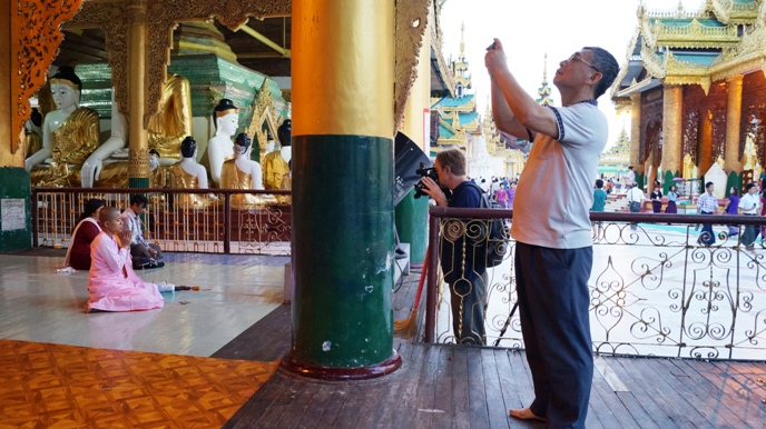 Look past the Asian dude at the guy behind him. The set up a huge video camera to record a nun praying, completely disregarding that she is facing the Shwedagon Pagoda, one of the most sacred sites in Myanmar. From that angle, he is completely disrupting her prayer.
