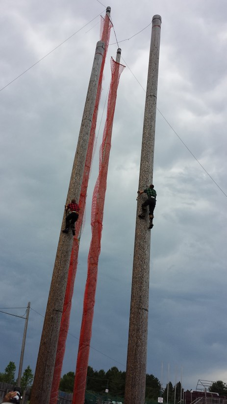 Lumberjacks climbing poles. Photo Credit: Linda Askomitis