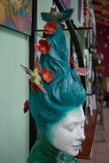 Sculpture of woman's head with blue hair, flowers and bird