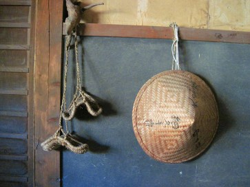 A traditional hat and straw sandals are displayed on the wall of one of the wayside inns known as minshuku along Japan's Nakasendo Way. Photo by Peter Mandel