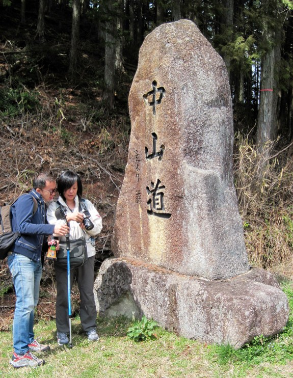 """Two walkers check out a photo next to one of the stone signs marking the route of the Nakasendo Way. The three Japanese characters can be translated to """"meadow,mountain, road."""""""