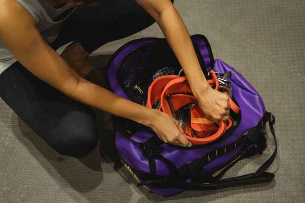 unrecognizable woman packing safety belt in bag after training