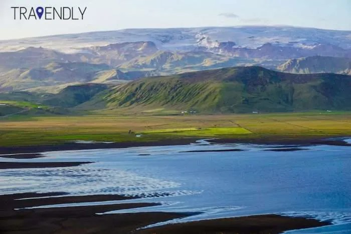 Solheimajokull glacier, black sand beach and green countryside in Iceland