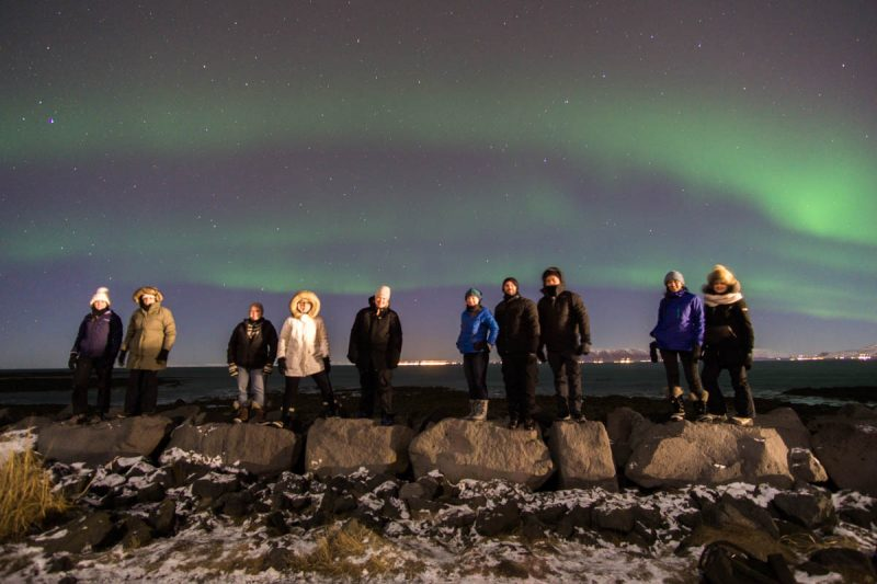 Group shot on rocks under Northern Lights