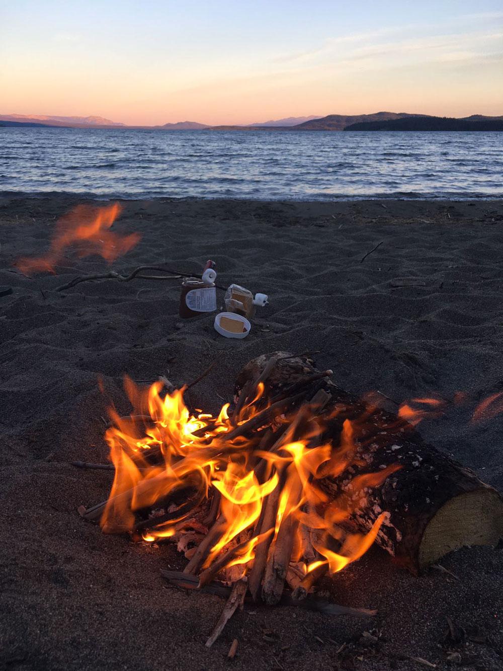 Feu de camp et marshmallows au bord d'un lac