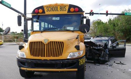 Black SUV t-bones school bus on Becker Rd