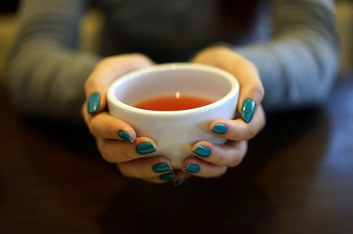 hands holding a cup of asthma tea
