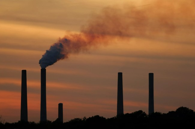 Smoke from a powerplant in front of a sunset.