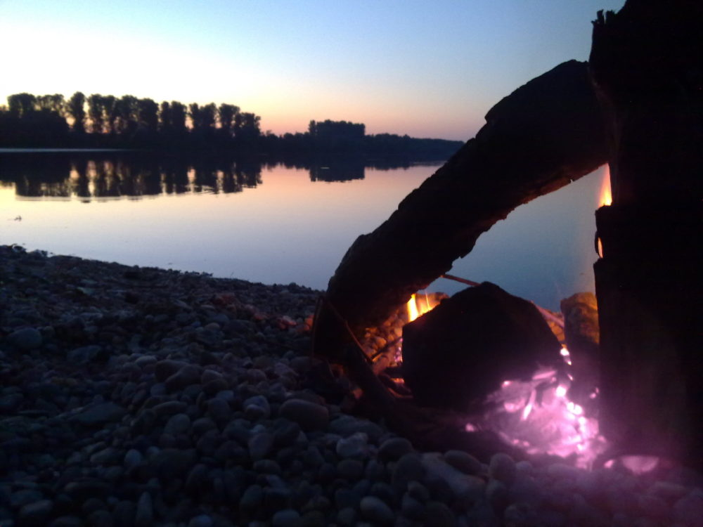 Sonnenuntergang mit Lagerfeuer am See