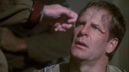 Archer com maquiagem alienígena sendo desmascarado