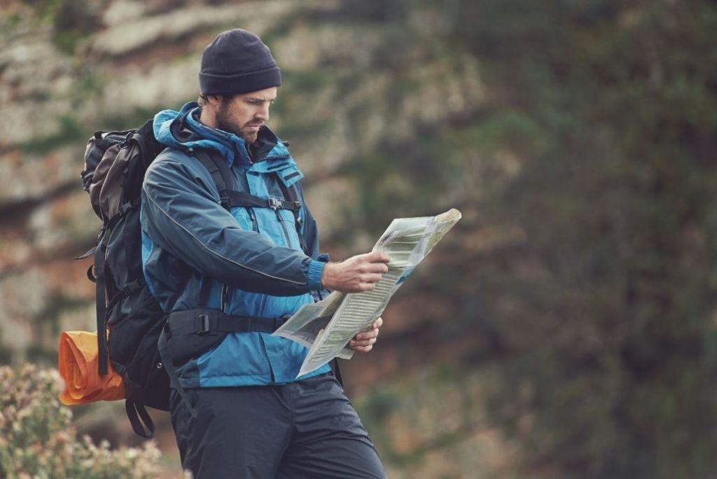 un randonneur avec une carte topographique