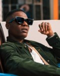 Wizkid's angry face after a fan pulled his leg until he fell on stage at Starboy Fest