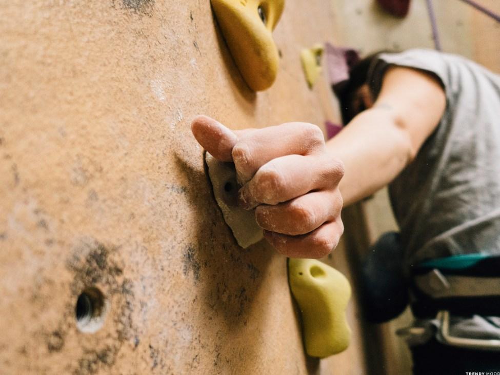 Mains de grimpeuse sur une prise d'escalade