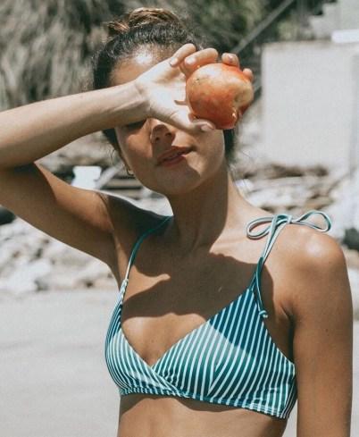 Jeune femme en maillot de bain qui mange une pomme