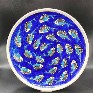 Grande Assiette/Plateau en céramique Motif Poisson, elle est émaillée et entièrement fait main par des artisans iraniens. Les méthodes de fabrication traditionnelle rendent cette assiette résistante aux variations de températures. Diamètre 35cm. C'est un objet peint et émaillé entièrement à la main ce qui le rend unique.