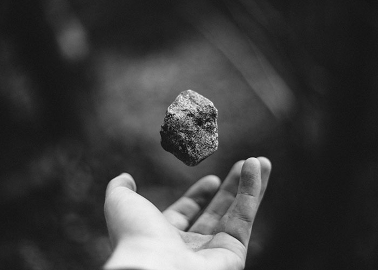 hand tossing stone up in the air black and white
