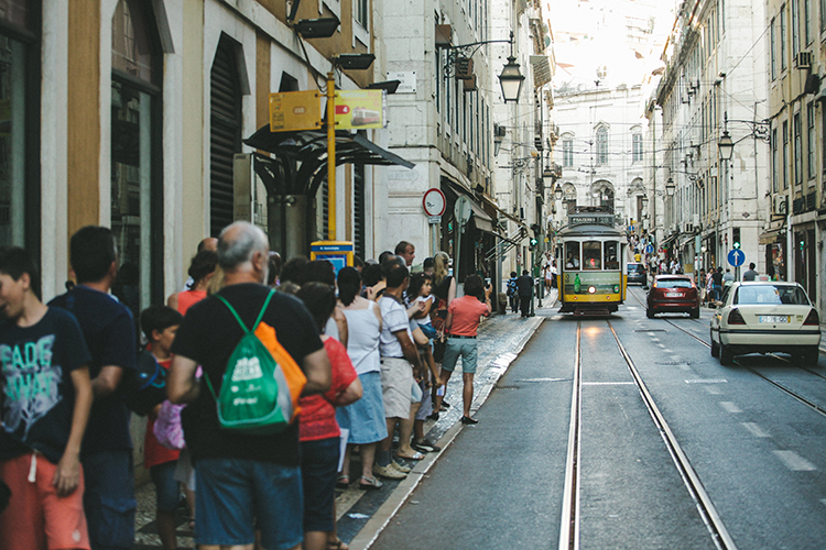 streetcar on a busy street with many people waiting