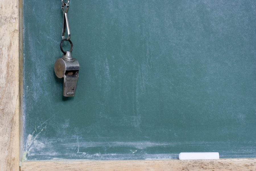 A whistle hanging against a green chalkboard