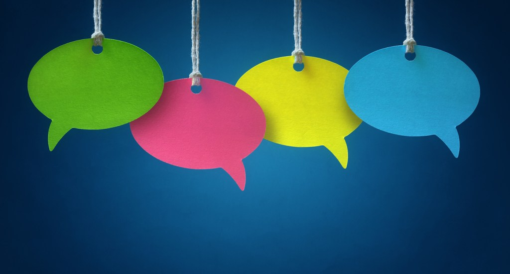 Blank colorful speech bubbles hanging from a cord over blue background