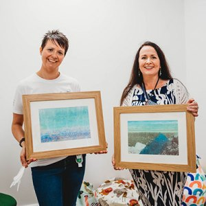 Susan Macmillan, Tributes Marketing Director, presents two framed Waterline Art prints to Kayla Shepherd for Andys Angels Reflection Room