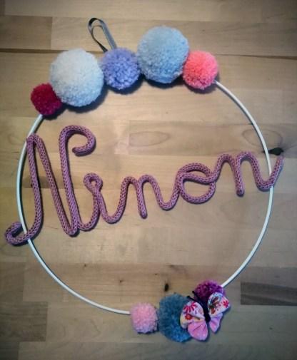 Ninon en tricotin sur une couronne de pompons