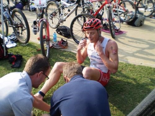 Stoltz, champion X-Terra, en T1. Ici, des médecins lui administrent des premiers soins après qu'il se soit ouvert le pied lors de la natation sur une poutrelle submergée.  Au lieu de faire son précieux et d'abandonner la course, il dit aux médecins de se dépêcher, enfile son matos avant de poursuivre et d'éventuellement gagner la course.  Source : http://www.conradstoltz.com/