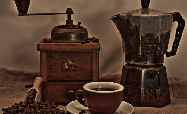 old coffee grinder with coffee pot and cup of coffee
