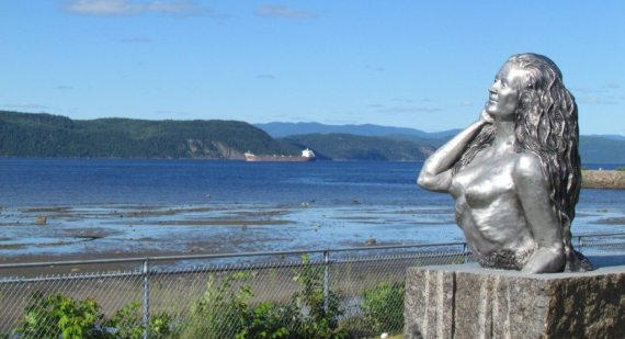 Outside of the Museum of the Fjord in Saguenay is an awesome statue of a mermaid and the view to the bay with the large boats is awesome.