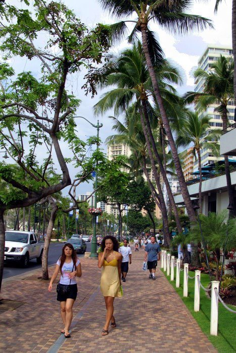Hawaiian girls walking on the busy promenade in Waikiki. This busy street was full of pedestrians in a leisurely stroll around the shops and boutiques of Waikiki,
