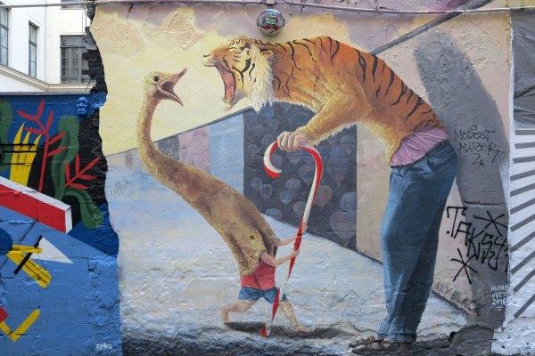 Katutaideteos, jossa puoliksi tiikeri oleva aikuinen ja strutsin päätä kantava lapsi ovat vastakkain, näennäisesti polkkakaramellin näköisestä kävelykepistä riidellen.