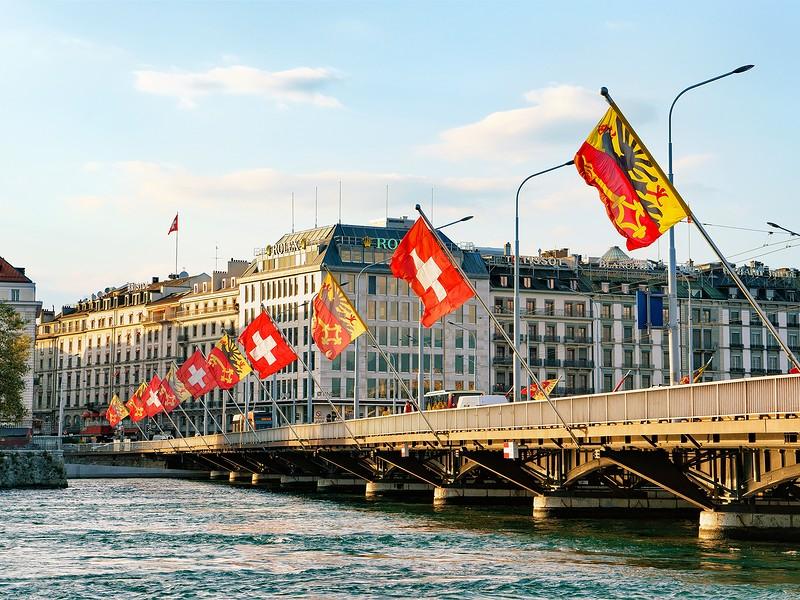 Geneva Lake and Mont-Blanc bridge with flags Geneva city center