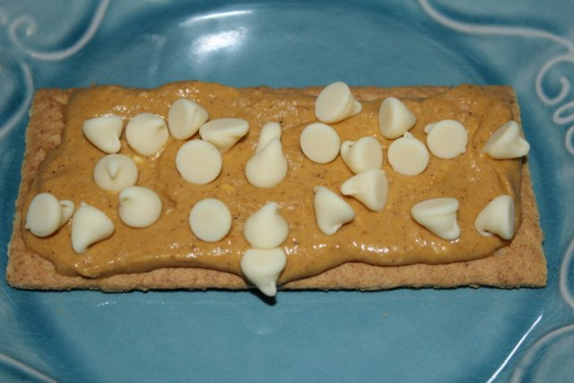 Pumpkin spread and white chocolate on a graham cracker for pumpkin s'mores.