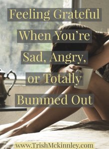 Women's head resting on her knees with title overlay: 'Feeling grateful when you're sad, angry or totally bummed out