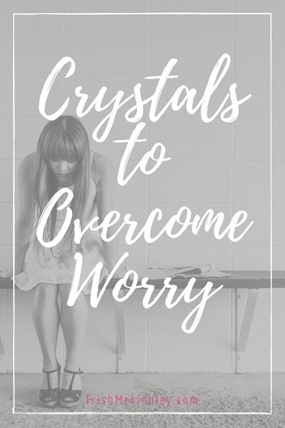 Girl sitting down and looking sad with title overlay 'Crystals to Overcome Worry'