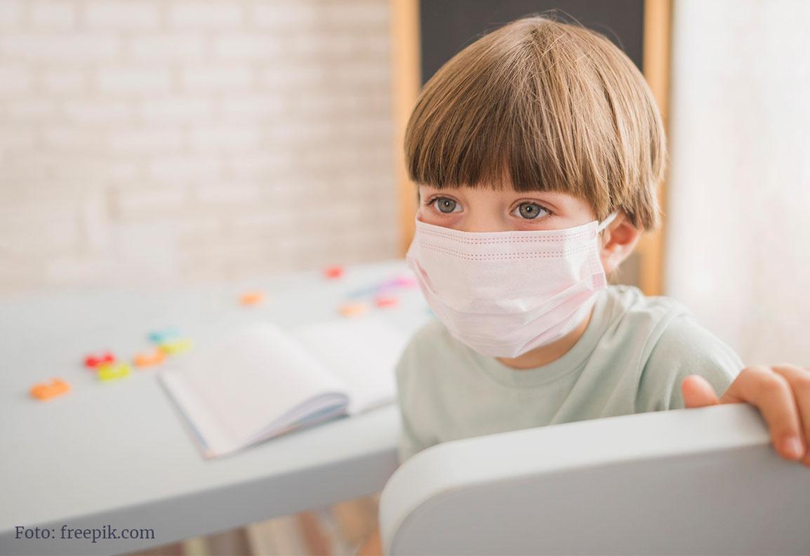 Schulkind mit Atemschutzmaske vor einem Schulbuch