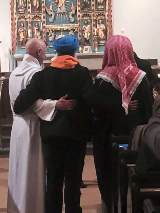 A Christian, Muslim and Sikh share a hug at St James Church, Hebden. Credit: Rachel Brandwood