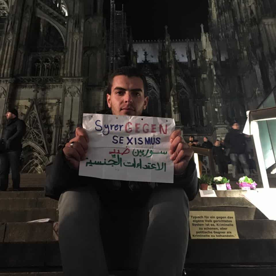 A Syrian man holds a sign showing respect for German culture and condemning attacks by his countrymen.