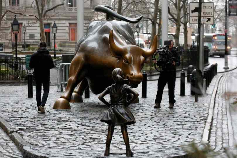 Small girl fearlessly faces Wall Street bull