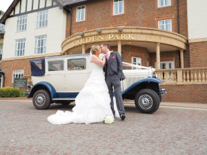 Bride and Groom with the wedding car at the main entrance to Carden park
