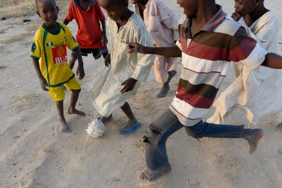 Children in the Bakassi IDP camp outside of Maiduguri play a game of pickeup soccer.