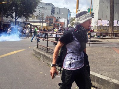 A protestor in Bogotá screams at police as tear gas wafts in the background. Protests over unfair trade practices, which have allegedly hurt Colombia's farmers, quickly turned violent.