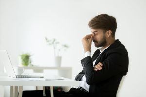 Businessman at desk with headache
