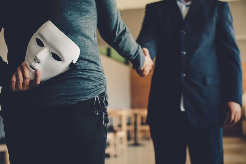 Employee shaking hands while holding a mask behind back