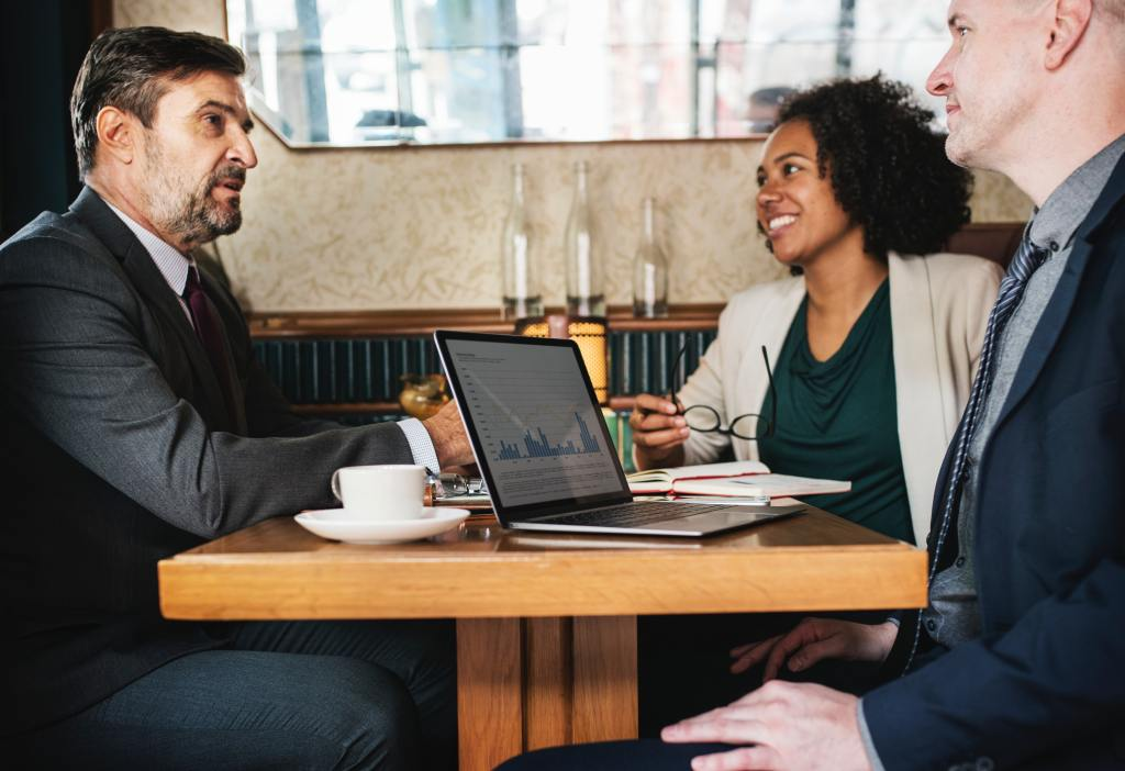 Startup business owner taking time to communicate with employees at coffee shop